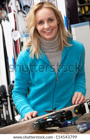 Female Sales Assistant With Skis In Hire Shop - stock photo