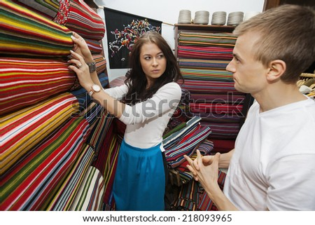 Female salesperson assisting man in textile store - stock photo