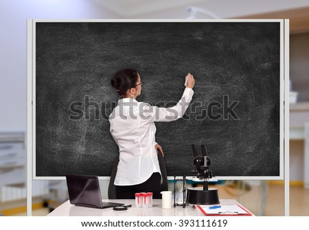female scientific researcher drawing on blank blackboard in laboratory - stock photo