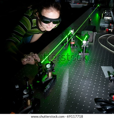 female scientist doing research in a quantum optics lab - stock photo