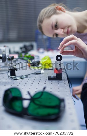 female scientist doing research in a quantum optics lab (color toned image) - stock photo