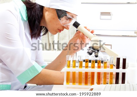 female scientist microscoping in the life science research laboratory (genetics, biochemistry, forensics, microbiology) - stock photo
