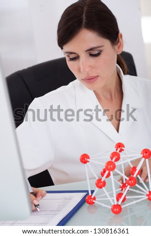 Female Scientist Sitting In Laboratory And Writing On Clipboard - stock photo
