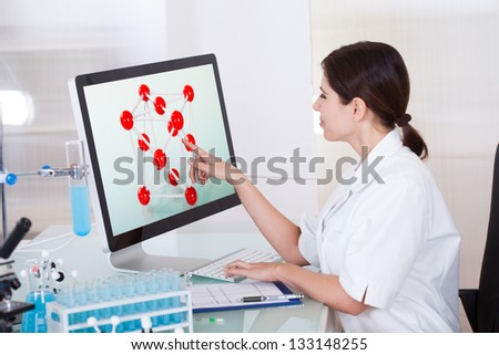 Female Scientist Touching Computer Screen In Lab - stock photo