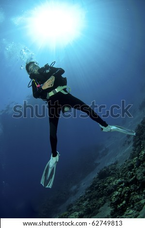 female scuba diver enjoys a dive in the red sea - stock photo