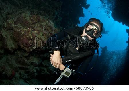 female scuba diver in a cave - stock photo