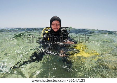 female scuba diver on the surface - stock photo
