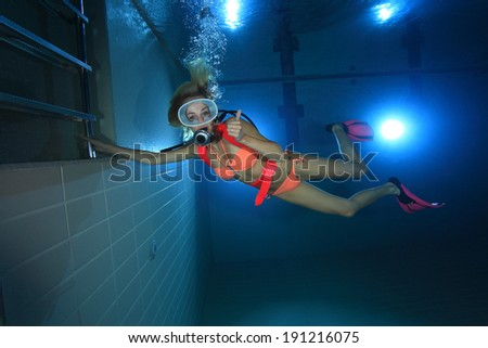 Female scuba diver show signal underwater in the pool - stock photo