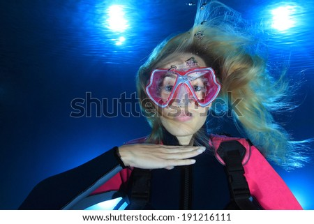 Female scuba diver show the underwater signal for out of air  - stock photo