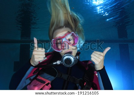 Female scuba diver smiling underwater in the pool - stock photo