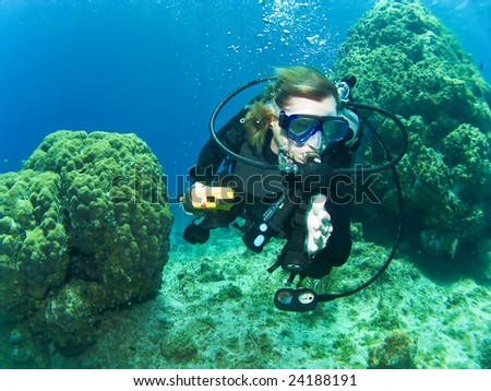 Female Scuba Diver Swimming between the Reef in Cayman Brac - stock photo