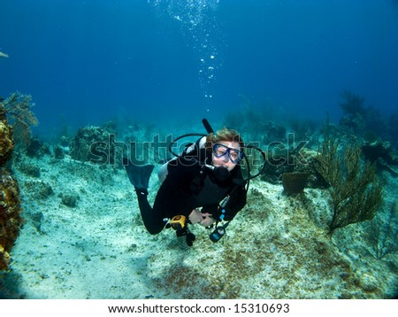Female Scuba Diver swimming while looking at the Camera - stock photo
