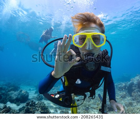 Female scuba diver underwater showing ok signal - stock photo