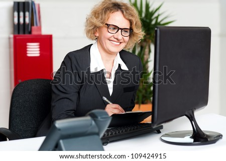 Female secretary wearing eyeglasses holding pen and looking at computer screen