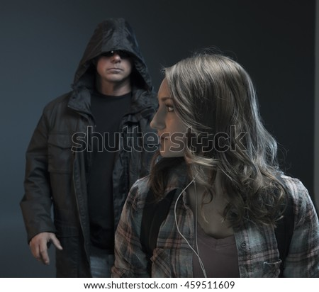 FEMALE SELF DEFENSE SERIES- Scary man grabs a girl on her phone.  Teenage Girl gets attacked by a stranger.Studio photo with filter applied. - stock photo