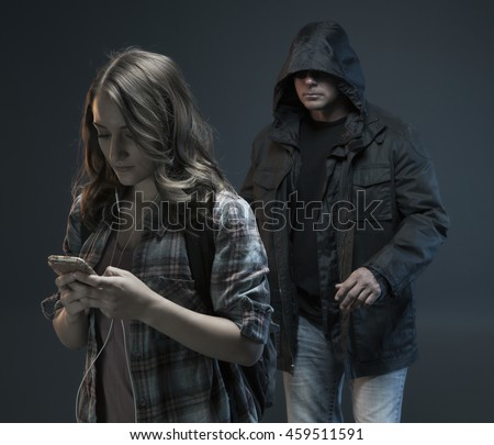 FEMALE SELF DEFENSE SERIES- Teenage Girl gets attacked by a stranger. He sees her texting and walking.Studio photo with filter applied. - stock photo