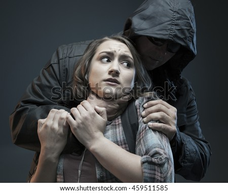 FEMALE SELF DEFENSE SERIES- Teenage Girl on a cell phone gets attacked by a stranger who is trying to choke her. Studio photo with filter applied. - stock photo