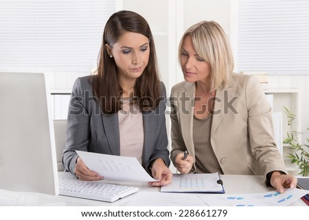 Female senior and junior managers sitting at desk working together in a business team. - stock photo