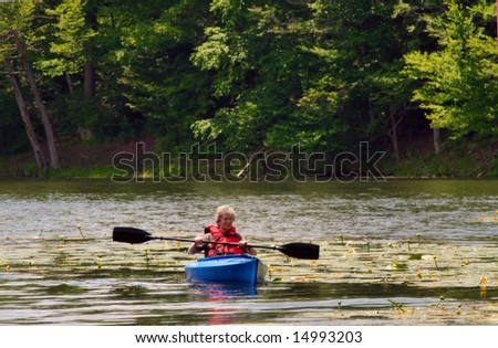 Female senior citizen kayaking on a pond - active retirement. - stock photo