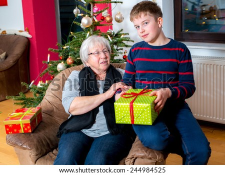 female senior has a christmas present for her grandson - stock photo