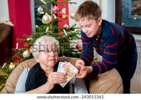 female senior has a money gift for her grandson - stock photo