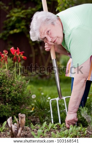 Female Senior in the garden with pitchfork - stock photo