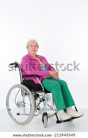 female senior in wheelchair in front of white background  - stock photo