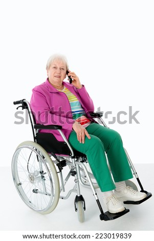 female senior in wheelchair is calling  - stock photo