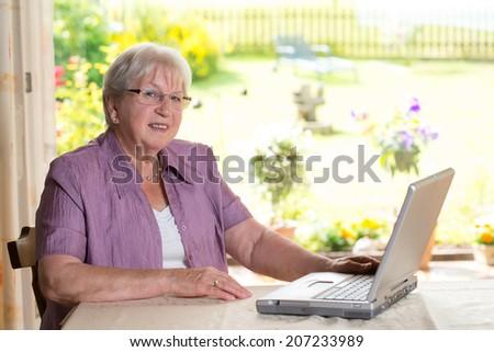 female senior is using computer - stock photo