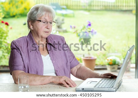female senior is using computer at home - stock photo