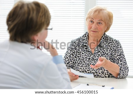 Female senior patient tells the doctor about her health complaints - stock photo