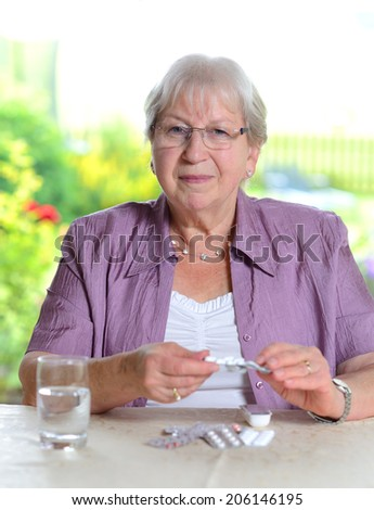 female senior with drugs is smiling - stock photo