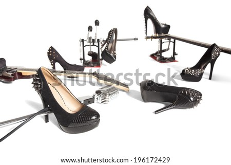 Female shoe and musical instruments scattered over white background - stock photo