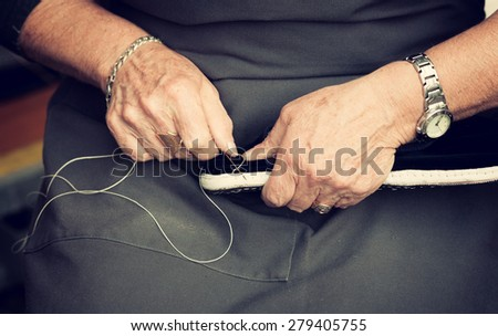 Female shoemaker sews shoes on his knees. - stock photo
