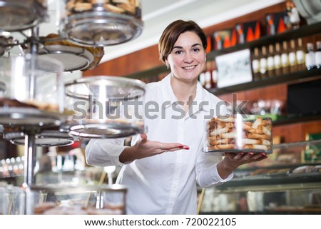 Female shop assistant demonstrating delicious rolled buns on tray in confectionery