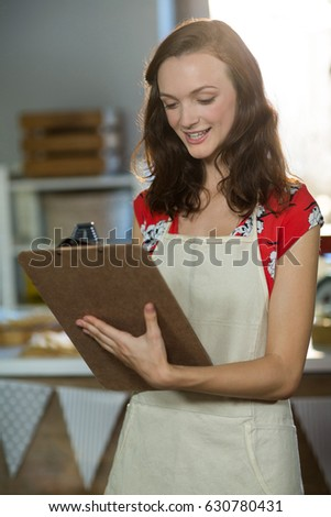 Female shop assistant writing on the clipboard at the counter in grocery shop