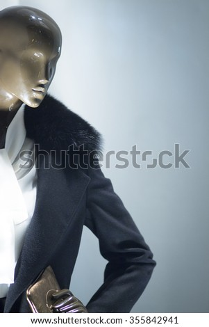 Female shop dummy fashion mannequin in department store boutique window wearing current women's fashions in clothes. - stock photo