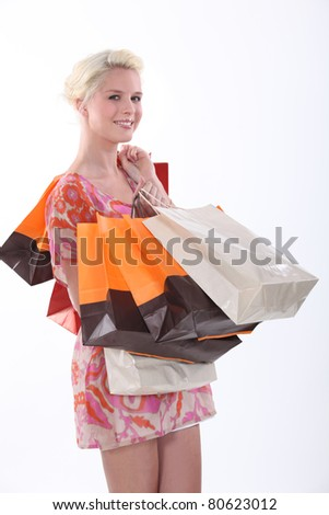 Female shopper and her many bags - stock photo