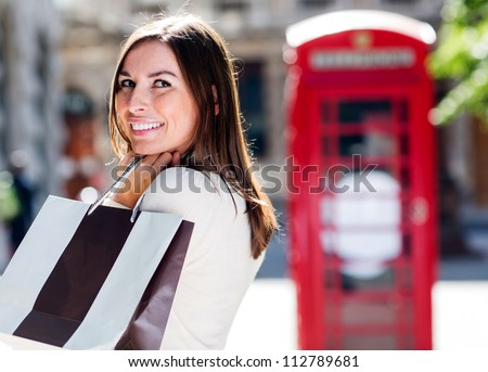 Female shopper daydreaming and holding shopping bags - stock photo