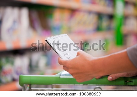 Female shopper holding checklist with trolley at supermarket - stock photo