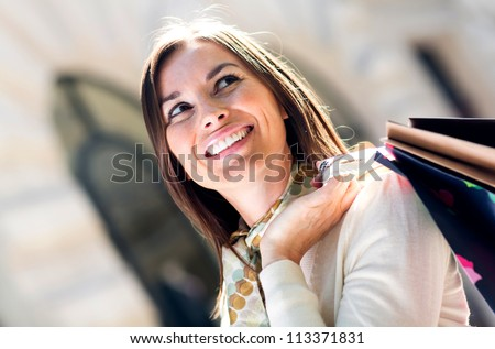 Female shopper holding shopping bags and looking happy - stock photo