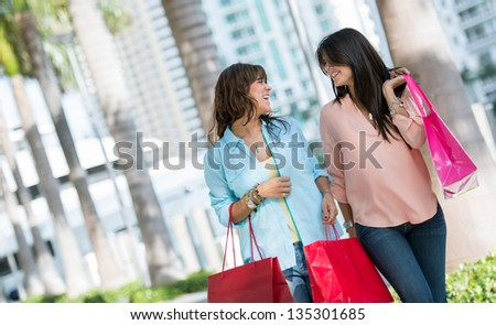 Female shoppers looking very happy carrying bags - stock photo