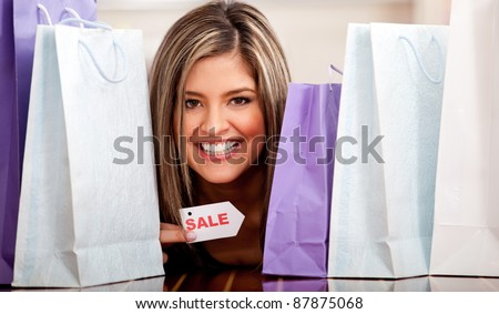 Female shopping on sale with a bunch of bags and smiling