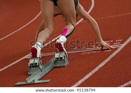 Female short distance runner  is in start position - stock photo