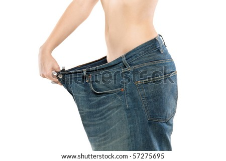 Female showing her lost weight by putting on an old jeans - stock photo