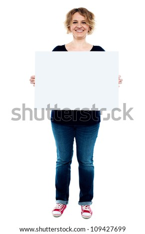 Female showing white blank advertising board, full length portrait - stock photo