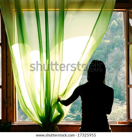 female silhouette at open window in old hotel - stock photo