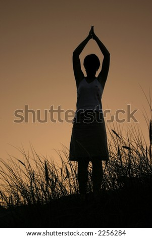 female silhouette celebrating summer sunset, PERSON ISN'T IDENTIFABLE - stock photo