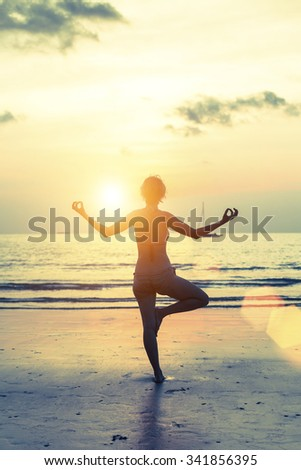 Female silhouette in yoga meditation pose at sunset. - stock photo