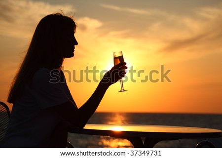 Female silhouette on sunset at  table with  glass in hand - stock photo